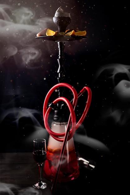 煙と黒の背景に果物と赤い釜 Premium写真