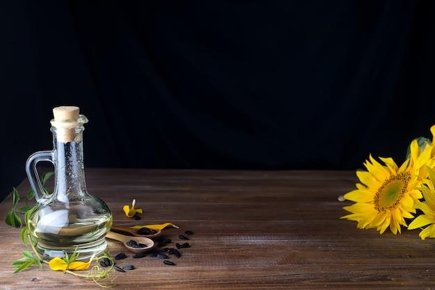 木製のスプーンとヒマワリ油と美しい黄色のひまわりのひまわりの種 Premium写真