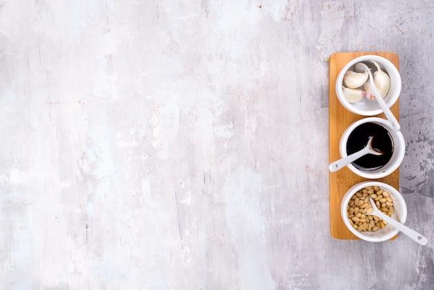 Специи кедровые орехи, соевый соус и чеснок на миске серый каменный фон с копией пространства Premium Фотографии