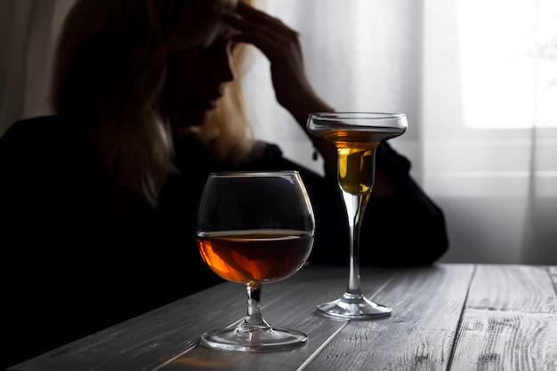 Женщина, пить алкоголь в одиночку, глядя в окно. Premium Фотографии