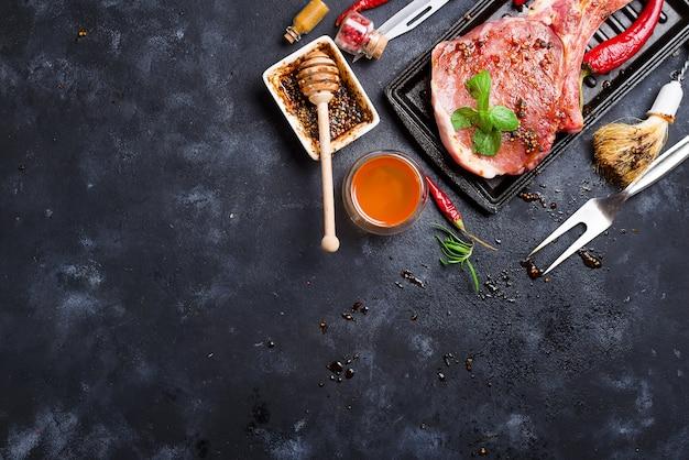 調味料、ガーニッシュ、成分を含む生のステーキとフライパン Premium写真