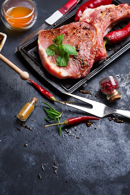 生のステーキとフライパン、調味料、ガーニッシュ、食材を暗い素朴な背中に Premium写真