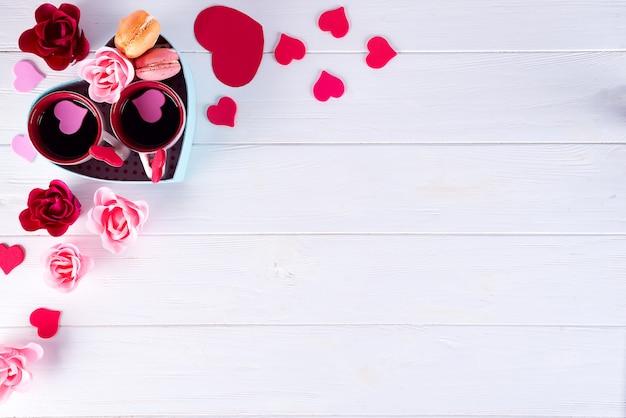 Две чашки кофе, миндальное печенье, цветы в форме коробки сердца на белом фоне. Premium Фотографии
