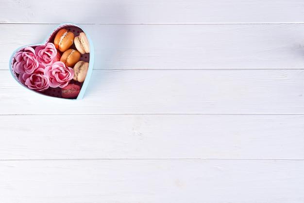 マカロンと白い木製の背景、バレンタインの日にバラのハートボックス Premium写真