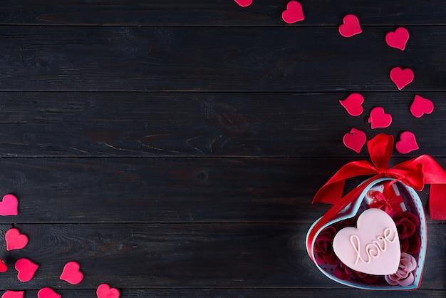 暗い背景の木のハートボックスにハートの形のバレンタインのクッキー Premium写真