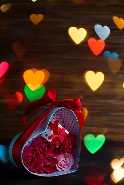 赤いハートと暗い背景の木のギフトボックスにバラとバレンタインの背景 Premium写真