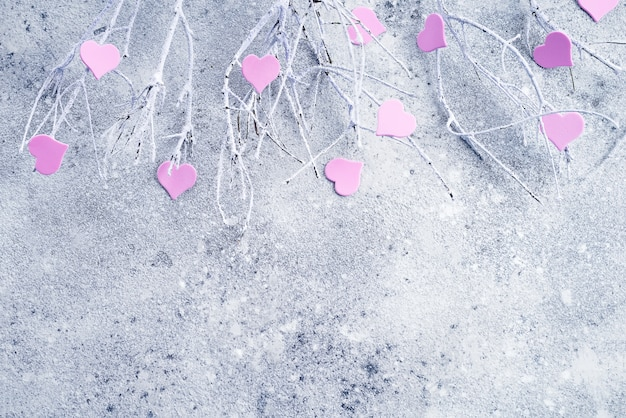 コンクリートの背景にピンクの心と雪の中で枝 Premium写真