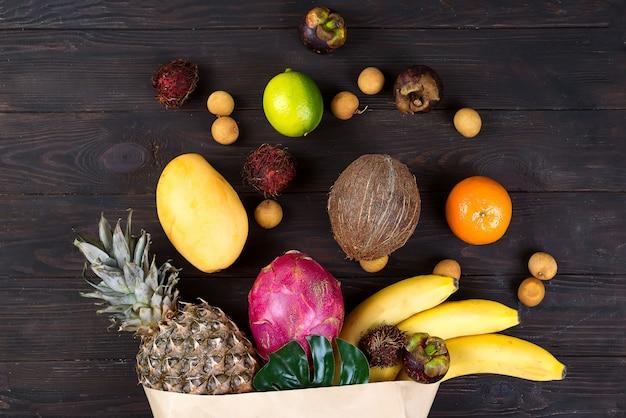 Бумажный пакет различных здоровых тропических фруктов на темном деревянном фоне. вид сверху. Premium Фотографии