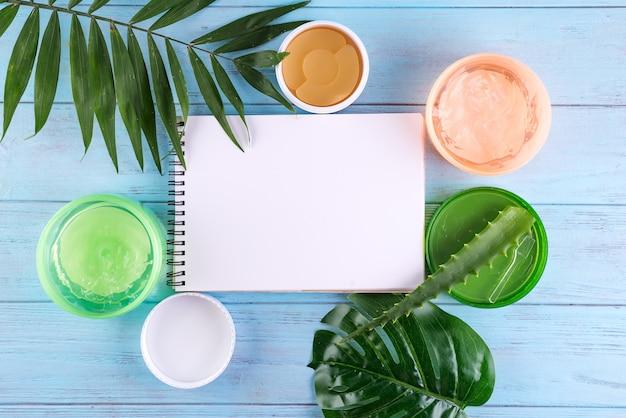 カタツムリ、アイパッチ、青い木製の背景に紙のノートと瓶の中のアロエベラジェルのゲル。コピースペース Premium写真