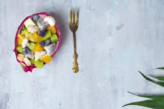 エキゾチックなフルーツサラダは、石の背景、コピースペースのヤシの葉の上半分のドラゴンフルーツで出されました。平置き Premium写真