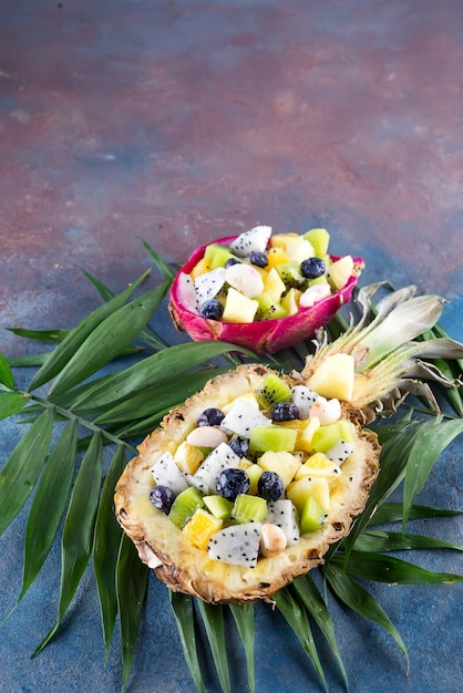 エキゾチックなフルーツサラダは、石の背景にヤシの葉の上にパイナップルの半分で提供しています。健康食品 Premium写真