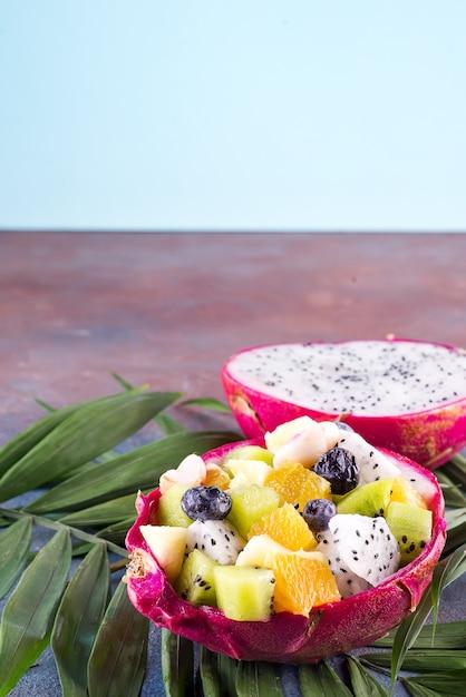 エキゾチックなフルーツサラダ、コピースペースの石の背景にヤシの葉の半分のドラゴンフルーツ Premium写真