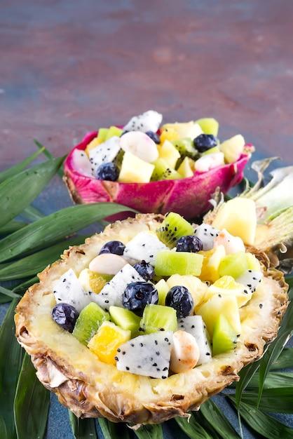 エキゾチックなフルーツサラダを石の背景にヤシの葉の上にパイナップルの半分で提供しています Premium写真
