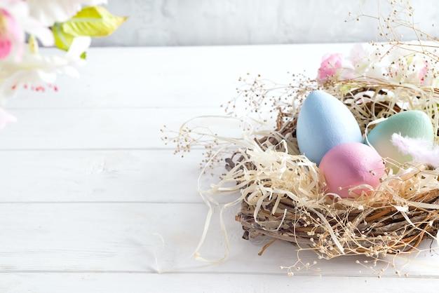 明るい背景に巣の中のカラフルな卵を持つ美しい花 Premium写真