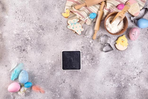 小麦粉、卵、イースターの艶をかけられたクッキーと石の背景にベーキングアクセサリー。 Premium写真