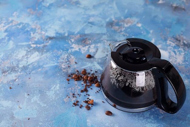コーヒー豆でいっぱいのコーヒーメーカーポット Premium写真