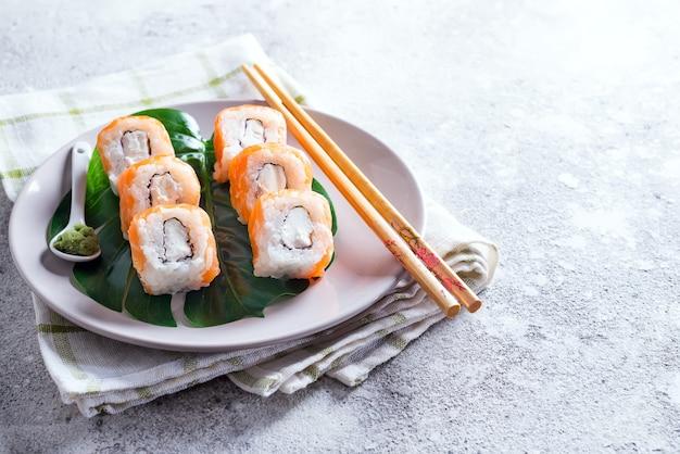 フィラデルフィアは箸で皿の上に古典的なロール。日本の寿司料理 Premium写真