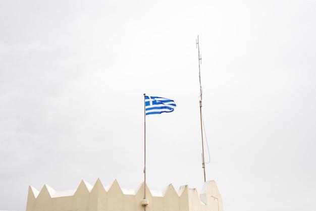 青い空、コス、ギリシャに対して手を振っている旗竿にギリシャの国旗 Premium写真