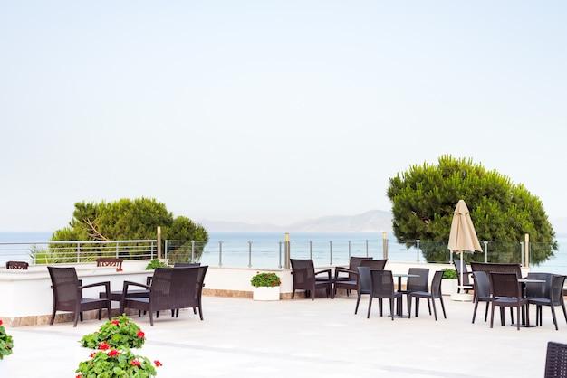 朝は屋上の屋外カフェバーで、海の景色を望む居心地の良い籐製のテーブル、 Premium写真