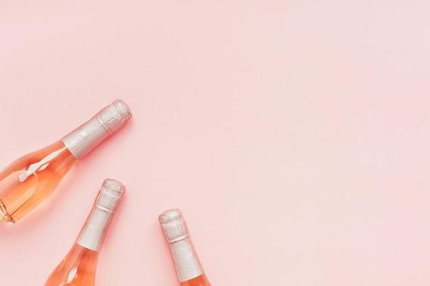 Бутылка розового шампанского на розовом фоне Premium Фотографии