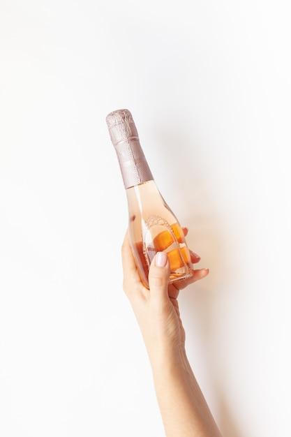 Бутылка розового шампанского в женской руке Premium Фотографии