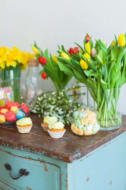明るいマカロンと木製のテーブルのカップケーキ Premium写真