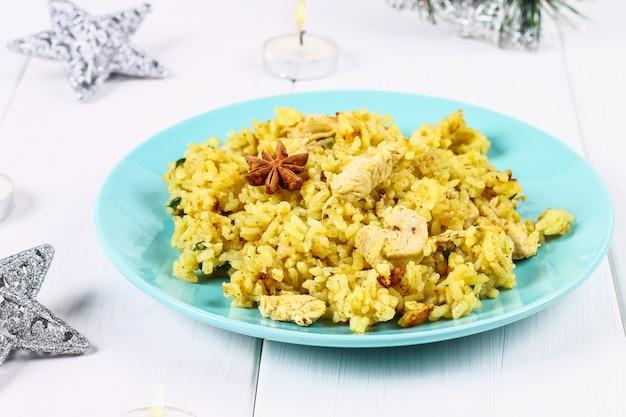 Индийские бирьяни с курицей, йогуртом и специями в плите на деревянном столе. новогоднее, рождественское блюдо Premium Фотографии