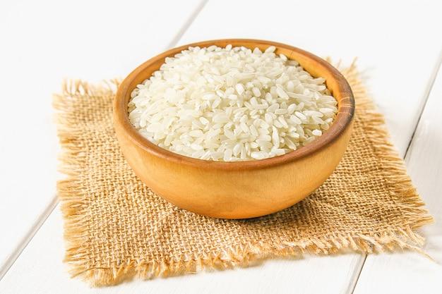 ボードの白い木製のテーブルに生の白米の粒。料理の食材。 Premium写真