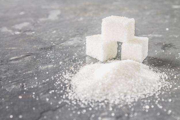 暗い灰色の背景に砂糖と砂糖の砂のキューブ。 Premium写真