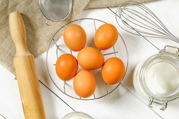 生の茶色の鶏の卵、牛乳、砂糖、小麦粉、泡立て器、麺棒 Premium写真