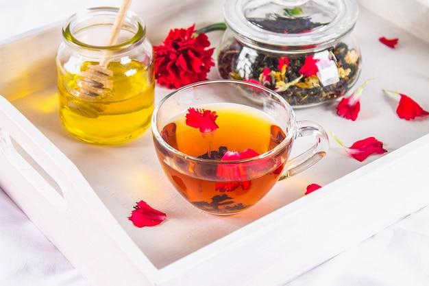 一杯のお茶、蜂蜜の缶、そしてベッドの白いトレイの上の黒のハーブティーの瓶。 Premium写真