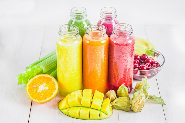 Разноцветные смузи в бутылках из манго, апельсина, банана, сельдерея, ягод, на деревянном столе. Premium Фотографии