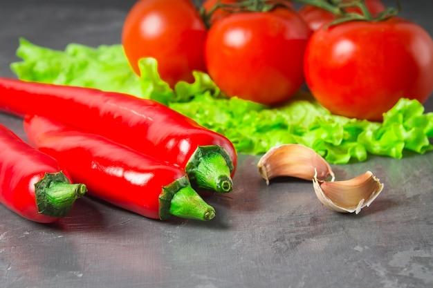 赤唐辛子、トマト、サダット、灰色の大理石の背景にニンニク。 Premium写真