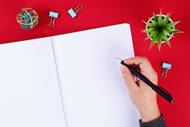 赤い背景の上のノート。 Premium写真