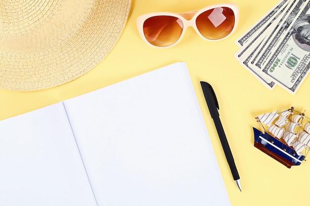黄色の背景上のノートブック。夏のコンセプトです。休暇のための準備 Premium写真