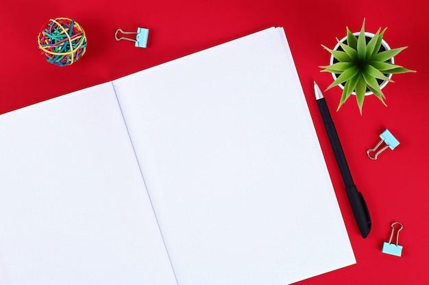 赤いテーブル、植物、ペンの空白のメモ帳。 Premium写真