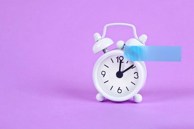 Белый будильник на фиолетовой пастели Premium Фотографии