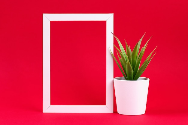 赤いバーガンディの背景に白いフレームに白い小さな鍋に人工の緑の芝生。 Premium写真