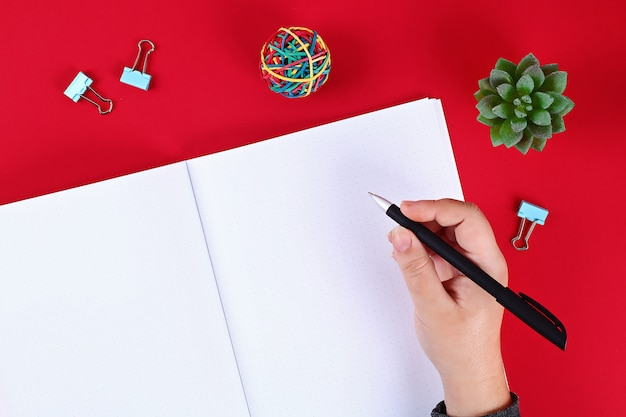 赤いテーブル、植物、ペンに空白のメモ帳。トップビュー、フラットレイアウト。モックアップ、スペースをコピーします。 Premium写真