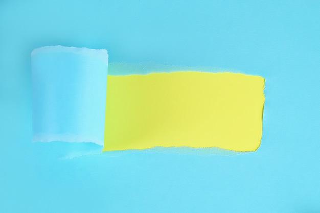 メッセージ用のスペースと引き裂かれた色の包装紙。背景の紙に穴をリッピングしました。コピースペース Premium写真