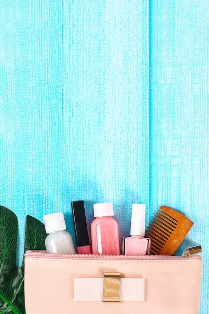 青い木製の表面に化粧品袋の化粧品。 Premium写真