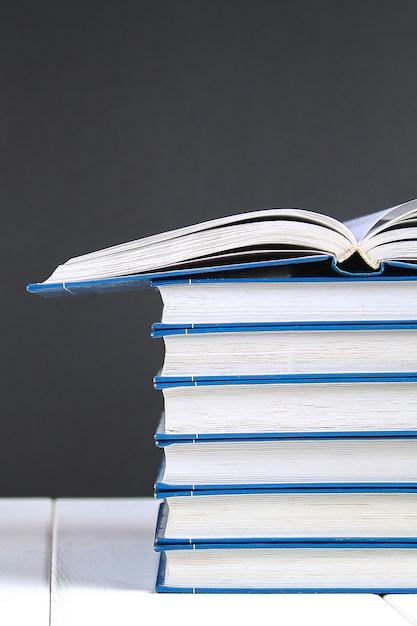 黒板背景の本のスタック。山の上に隠された本。 Premium写真