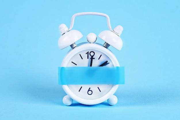 白い目覚まし時計パステルブルーの背景。クロックに空白の付箋。スペースコピー。最小限のコンセプト。 Premium写真