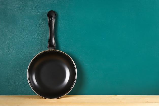 青緑色の背景に木製の棚に黒のフライパン。キッチン用品。 Premium写真