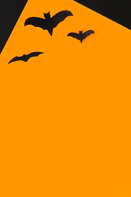 ハロウィーンのコンセプト。オレンジ色の背景のコウモリ。 Premium写真