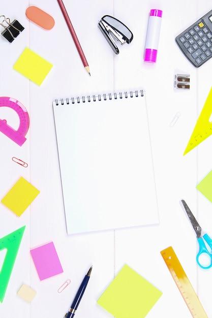 Пустая страница тетради окруженная канцелярскими принадлежностями на белом деревянном столе. скопируйте пространство. Premium Фотографии
