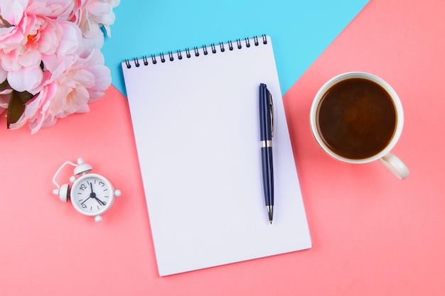 ピンクのパステル調の背景に青いペンを持つ空のノートブック。モックアップ、フレーム、テンプレート Premium写真