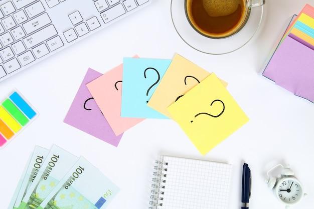 コーヒーとキーボードのマグカップの横に白い机の上に疑問符が付いたステッカーノート Premium写真