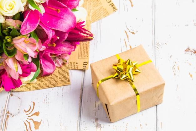 Подарок в коробке и букет цветов на белом деревянном столе. вечеринка в честь дня рождения Premium Фотографии