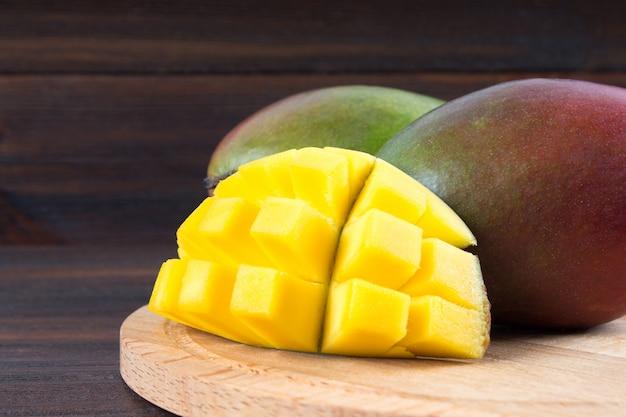木製の背景にトロピカルフルーツマンゴー、全体またはスライス。 Premium写真